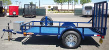 "Custom 5.5 x 10 Landscape Trailer with 3,500lb. GVWR, 3,500lb. Electric Braking Axle, 2-5/16"" A Frame Coupler, 2,000 lb. Tongue Jack, 1"" Pipe Top Rail, 4' Expanded Metal Gate, 15"" 5 on 4.5 Tires & Wheels, 2 x 10 Douglas Fir Deck, 24"" Formed Sheet Metal Sides, Dark Blue Painted Trailer and Undercarriage, Breakaway Kit, 7 Way Plug, Chrome Spare Tire and Wheel, Spare Tire Mount, Jet Ski Box on Front, Ramp Gate with Spring Assist, 4- 1/2"" D Rings"